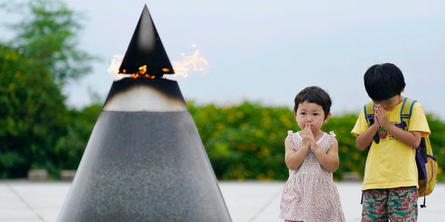 """Children pray in front of the """"Peace of Fire"""" at the Peace Memorial Park in Itoman, Okinawa, Japan, Tuesday, June 23, 2020. (Koji Harada/Kyodo News via AP)"""