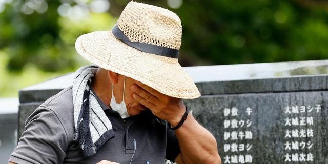 """A man cries as he visits """"Cornerstone of Peace"""" monument walls on which the names of all those who lost their lives, both civilians and military of all nationalities in the Battle of Okinawa are engraved, at the Peace Memorial Park in Itoman, Okinawa, Japan, Tuesday, June 23, 2020. (Kyodo News via AP)"""