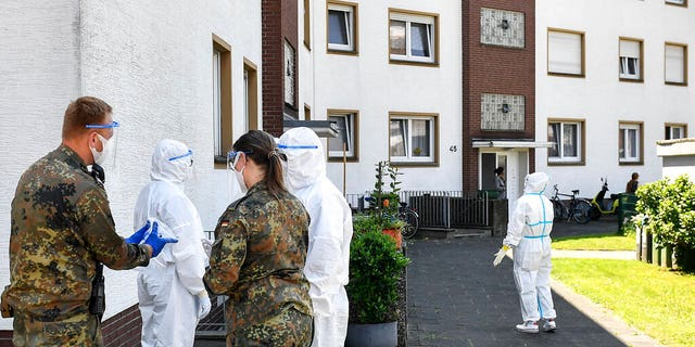 Medical staff and helpers from the German army take COVID-19 tests of Toennies employees and their families who are quarantined in Verl, Germany, Tuesday, June 23, 2020. Following the corona outbreak at meat processor Toennies in Rheda-Wiedenbrueck, the federal state authorities are massively restricting public life in the Guetersloh district with a lockdown.