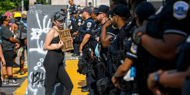 "A woman holds up a sign saying ""police the police"" as she confronts a police line while demonstrators protest on a section of 16th Street that has been renamed Black Lives Matter Plaza, Tuesday, June 23, 2020, in Washington, D.C."