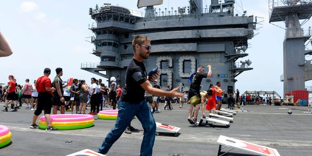 In this June 6, 2020, photo provided by the U.S. Navy, sailors participate in sporting events on the flight deck of the aircraft carrier USS Dwight D. Eisenhower (CVN 69). (Mass Communication Specialist Seaman Brennen Easter/U.S. Navy via AP)
