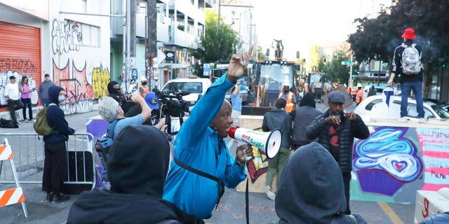 A man speaking in to a bullhorn urges protesters not to be violent after workers and heavy equipment from the Seattle Department of Transportation arrived at the the CHOP (Capitol Hill Occupied Protest) zone in Seattle, Friday, June 26, 2020, with the intention of removing barricades that had been set up in the area. Several blocks in the area have been occupied by protesters since Seattle Police pulled back from their East Precinct building following violent clashes with demonstrators earlier in the month.