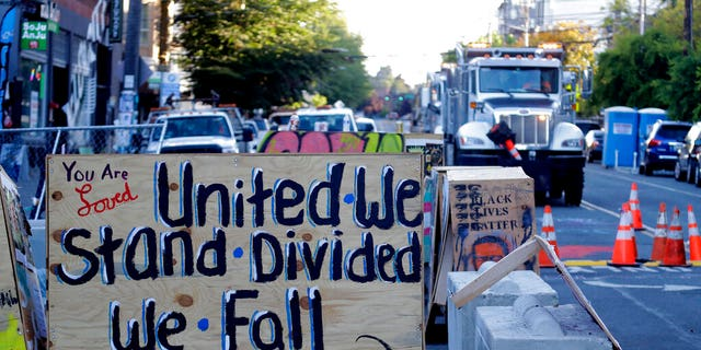 "A sign on a barricade reads ""United we stand divided we fall,"" as a truck and other heavy equipment from the Seattle Department of Transportation is staged at the CHOP (Capitol Hill Occupied Protest) zone in Seattle, Friday, June 26, 2020."