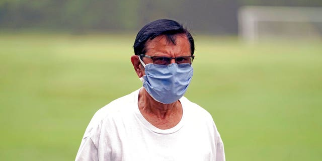 """Shiraz Merchant wears a mask as he walks in a park Friday, June 26, 2020, in Houston. The number of COVID-19 cases continues to rise across the state. Texas Gov. Greg Abbott has said that the state is facing a """"massive outbreak"""" in the coronavirus pandemic and that some new local restrictions may be needed to protect hospital space for new patients. (AP Photo/David J. Phillip)"""