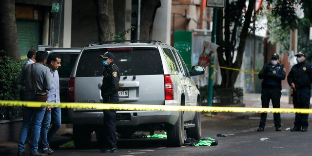 An abandoned vehicle that is believed to have been used by gunmen in an attack against Mexico City's chief of police is sealed off with yellow tape and guarded by responding officers on June 26. Heavily-armed gunmen attacked and wounded Omar Garcia Harfuch in a brazen operation that left an unspecified number of dead, Mayor Claudia Sheinbaum said. (AP)