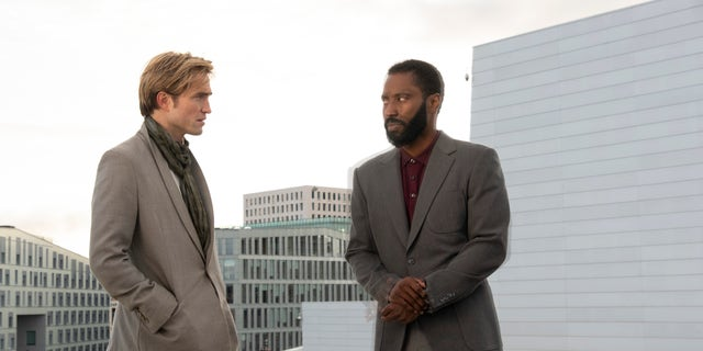 "Robert Pattinson, left, and John David Washington in a scene from ""Tenet."" Tom Cruise shared a video of his theatergoing experience on Twitter. (Associated Press)"