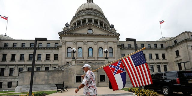 Don Hartness of Ellisville, walks around the Capitol carrying the current Mississippi state flag and the American flag, Saturday, June 27, 2020, in Jackson, Miss. (Associated Press)