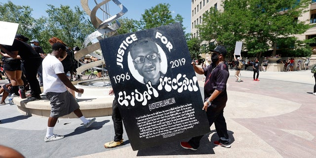 Demonstrators carry a giant placard during a rally and march over the death of 23-year-old Elijah McClain on Saturday outside the police department in Aurora, Colo. McClain died in late August 2019 after he was stopped while walking to his apartment by three Aurora Police Department officers. (AP Photo/David Zalubowski)