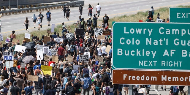 Demonstrators step on to Interstate 225 to block traffic during a rally and march over the death of 23-year-old Elijah McClain in Aurora, Colo. (AP Photo/David Zalubowski)