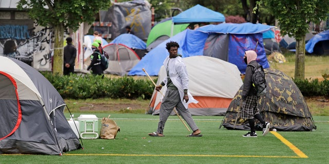 People walk among tents in a city park Sunday, June 28, 2020, in Seattle, where several adjacent streets are blocked off in what has been named the Capitol Hill Occupied Protest zone. Seattle Mayor Jenny Durkan met with demonstrators Friday after some lay in the street or sat on barricades to thwart the city's effort to dismantle the protest zone that has drawn scorn from President Donald Trump and a lawsuit from nearby businesses. (AP Photo/Elaine Thompson)