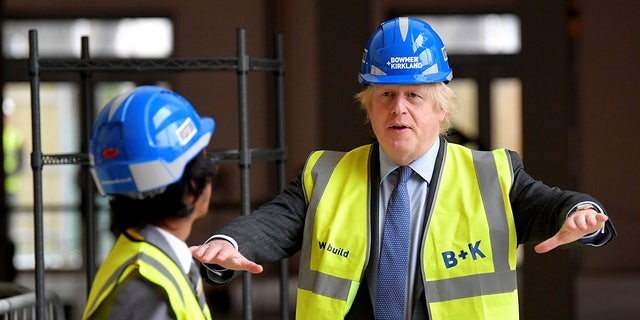 Britain's Prime Minister Boris Johnson talks with year 10 pupil Vedant Jitesh during a visit to the construction site of Ealing Fields High School in west London Monday
