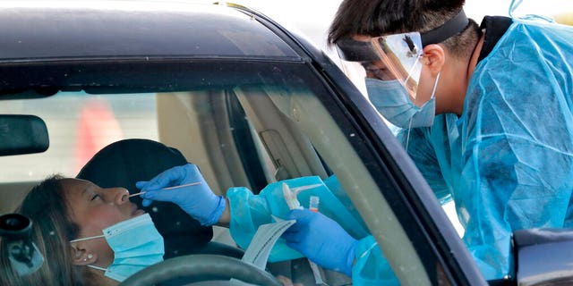 In this June 27, 2020, photo, people are tested in their in vehicles in Phoenix's western neighborhood of Maryvale in Phoenix for free COVID-19 tests organized by Equality Health Foundation, which focuses on care in underserved communities.