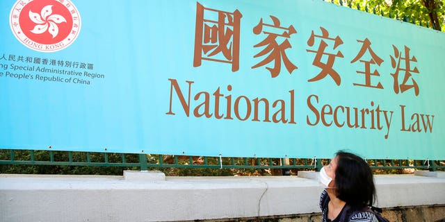 A woman walks past a promotional banner of the national security law for Hong Kong, in Hong Kong, Tuesday, June 30, 2020. China has approved a contentious law that would allow authorities to crack down on subversive and secessionist activity in Hong Kong, sparking fears that it would be used to curb opposition voices in the semi-autonomous territory.