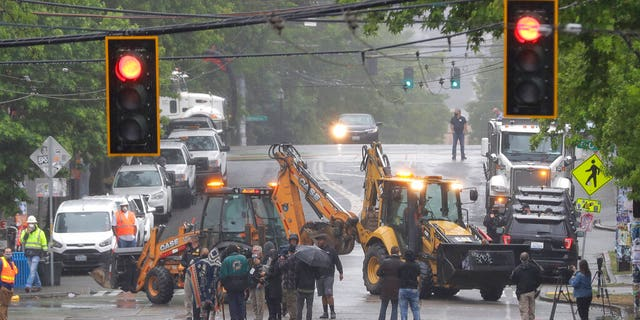 Seattle Department of Transportation workers remove barricades at the intersection of 10th Ave. and Pine St. on Tuesday at the CHOP zone in Seattle. Protesters quickly moved couches, trash cans and other materials in to replace the cleared barricades. (AP Photo/Ted S. Warren)