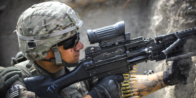 A US soldier from 2-12 Infantry Regiment out of Colorado Springs fires a machine gun at insurgent positions during a firefight on June 22, 2012 in the Pech Valley, Afghanistan - file photo.