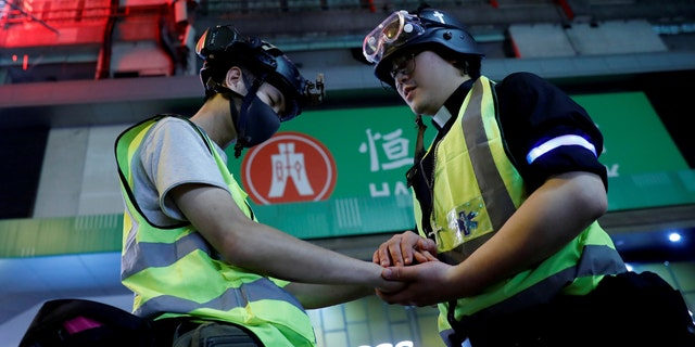 Pastor Alan Keung prays with a first aid volunteer who asked Alan to do so during an anti-government protest in Hong Kong, China, November 2019. (REUTERS/Kim Kyung-Hoon)