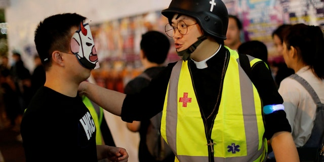 Pastor Alan Keung talks with a protester wearing a Halloween mask during an anti-government protest on Halloween in Hong Kong, China October 2019. (REUTERS/Kim Kyung-Hoon)