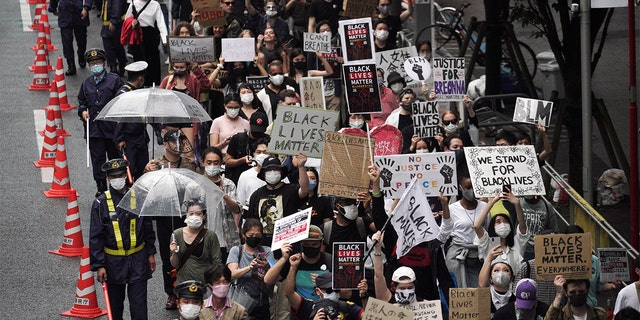 "People march to protest during a solidarity rally for the death of George Floyd in Tokyo Sunday, June 14, 2020. Holding handmade signs that read ""Black Lives Matter,"" several hundred people marched peacefully at a Tokyo park Sunday, highlighting the outrage over the death of Floyd even in a country often perceived as homogeneous and untouched by racial issues. (AP Photo/Eugene Hoshiko)"