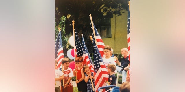Children in Baldwin, N.Y., line up to march with American flags in a town celebration on July 4, 1997.