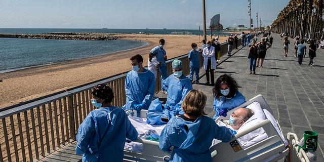 Hospital patient Isidre Correa is taken to the seaside by intensive health care staff outside the Hospital del Mar on June 03, 2020 in Barcelona, Spain.