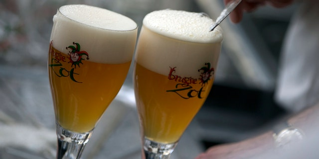 A worker scrapes the foam off of a glass of beer before serving in Bruges, Belgium. (AP)
