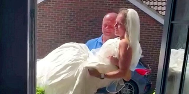 To mark the couple's wedding anniversary, Steph donned her old wedding dress and John proudly carried her through their front door as family and friends watched on.
