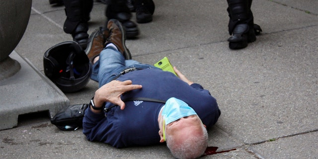 Martin Gugino, a 75-year-old protester, lays on the ground after he was shoved by two Buffalo, New York, police officers