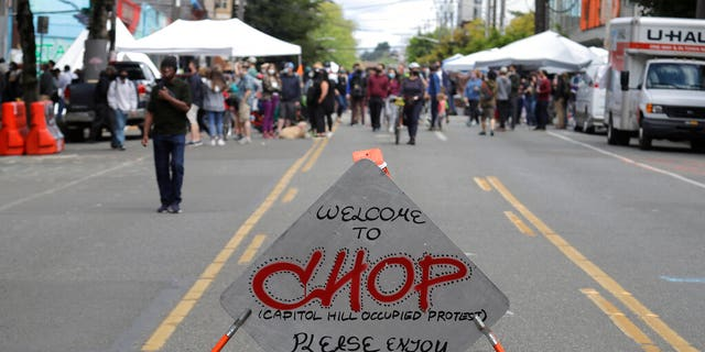 """A sign reads """"Welcome to CHOP,"""" June 14, inside what has been named the Capitol Hill Occupied Protest zone in Seattle.  (AP Photo/Ted S. Warren)"""
