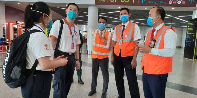 Members of a Chinese medical team are seen arriving at the airport in Phnom Penh, Cambodia, in April, to help conduct inspections amid new coronavirus protocols.