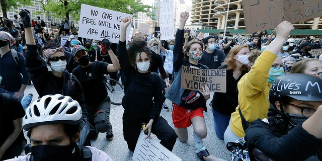 People get down on their knee during a protest over the death of George Floyd in Chicago, Saturday, May 30, 2020. Protests were held throughout the country over the death of Floyd, a black man who died after being restrained by Minneapolis police officers on May 25. (AP Photo/Nam Y. Huh)