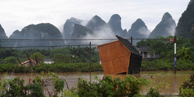 In this June 7 photo, released by Xinhua News Agency, facilities at a tourism site are toppled in the aftermath of a flood after heavy downpour in Yangshuo of Guilin, south China's Guangxi Zhuang Autonomous Region.