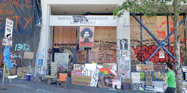 A person takes a photo of the Seattle Police East Precinct building, Monday, June 22, 2020, inside what has been named the Capitol Hill Occupied Protest zone in Seattle. (AP Photo/Ted S. Warren)
