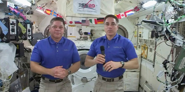 In this image taken from NASA video, NASA astronaut Chris Cassidy, right answers a question as fellow astronaut Robert L. Behnken listens during an interview aboard the International Space Station, Monday, June 29, 2020.
