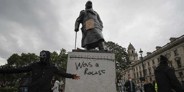 Protesters gather around a vandalized Winston Churchill statue in Parliament Square on Sunday. (AP)
