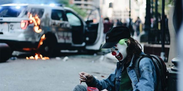 In the images, the masked mancan be seen handling a police vehicle's gas tank and later sitting and posing near the flaming SUV.(Courtesy: DOJ)
