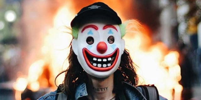 """Days after a man in a clown mask allegedly lit a Chicago police vehicle on fire in broad daylight, investigators tracked him down in part because he has the word """"PRETTY"""" tattooed across his neck. (Courtesy: DOJ)"""