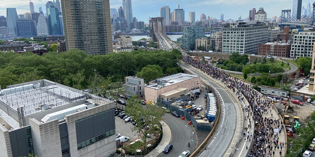 Protesters stream across the on-ramp to the Brooklyn Bridge as some drivers honk their horns in support Thursday. (James Rogers)