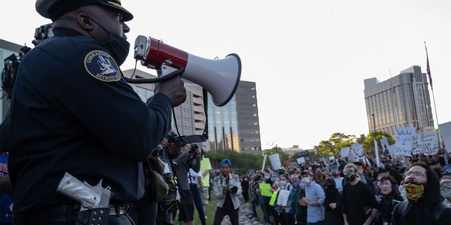 Police officers speaking to demonstrators in Detroit last May following a night of protests that saw several arrests and uses of tear gas by law enforcement. (SETH HERALD/AFP via Getty Images, File)