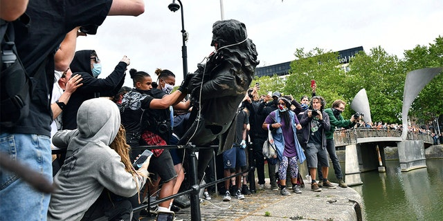 Protesters throw a statue of slave trader Edward Colston into the Bristol harbour, during a Black Lives Matter protest rally, in Bristol, England, Sunday June 7, 2020, in response to the recent killing of George Floyd by police officers in Minneapolis, USA, that has led to protests in many countries and across the US. (Ben Birchall/PA via AP)