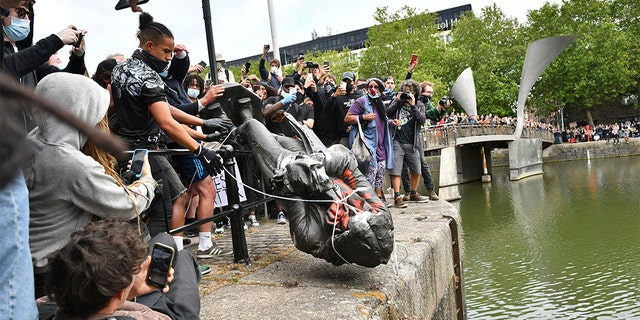 Protesters throwing the statue of slave trader Edward Colston into the Bristol harbor