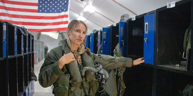 U.S. Air Force Capt. Emily Thompson, 421st Expeditionary Fighter Squadron pilot, dons flight equipment at the Aircrew Flight Equipment shop on Al Dhafra Air Base, United Arab Emirates, June 5, 2020. Thompson is the first female to fly an F-35A Lightning II into combat. She is currently deployed from Hill Air Force Base, Utah.