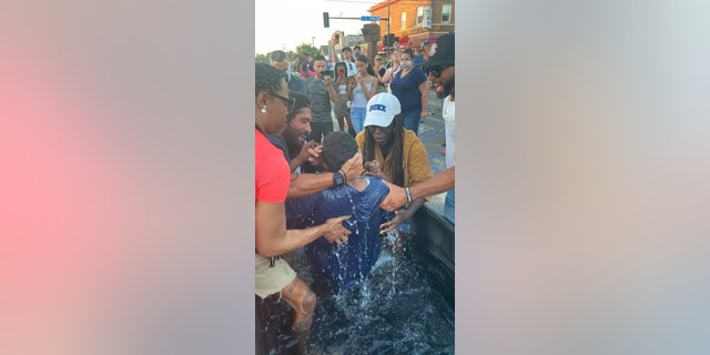 A person is baptized at the site where George Floyd was killed on Memorial Day at the hands of police officers. Several groups are holding daily services at that location offering hope and healing.