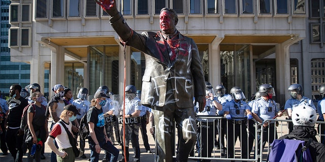 In this Saturday, May 30, 2020 photo police stand near a vandalized statue of controversial former Philadelphia Mayor Frank Rizzo in Philadelphia, during protests over the death of George Floyd, who died May 25 after he was restrained by Minneapolis police. Workers early Wednesday, June 3 removed the statue which was recently defaced during the weekend protest.