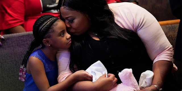 Roxie Washington holds Gianna Floyd, the daughter of George Floyd as they attend the funeral service for George Floyd at The Fountain of Praise church Tuesday, June 9, 2020, in Houston. (AP Photo/David J. Phillip, Pool)