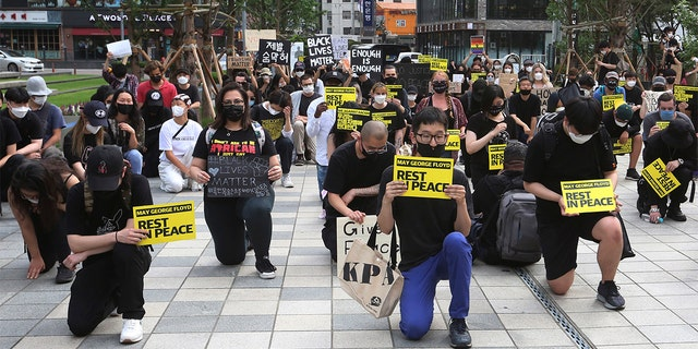 People kneel to protest during a solidarity rally for the death of George Floyd in Seoul, South Korea, Saturday, June 6, 2020. Floyd died after being restrained by Minneapolis police officers on May 25.(AP Photo/Ahn Young-joon)