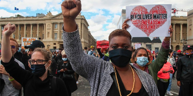 Demonstrators clench fists in Paris, France, Saturday, June 6, 2020, to protest against the recent killing of George Floyd, a black man who died in police custody in Minneapolis, U.S.A., after being restrained by police officers on May 25, 2020. Further protests are planned over the weekend in European cities, some defying restrictions imposed by authorities because of the coronavirus pandemic. (AP Photo/Michel Euler)