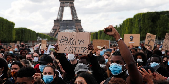 Hundreds of demonstrators gather on the Champs de Mars as the Eiffel Tower is seen in the background during a demonstration in Paris, France, Saturday, June 6, 2020, to protest against the recent killing of George Floyd, a black man who died in police custody in Minneapolis, U.S.A., after being restrained by police officers on May 25, 2020. Further protests are planned over the weekend in European cities, some defying restrictions imposed by authorities because of the coronavirus pandemic. (AP Photo/Francois Mori)