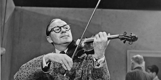 American comedian and actor Jack Benny (1894 - 1974) playing the violin, circa 1950s.