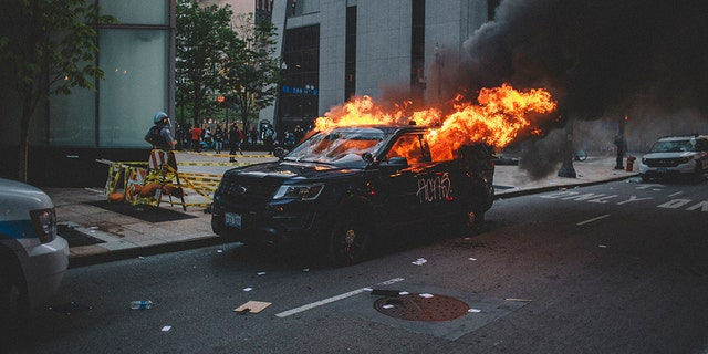 Protesters set fire to a police vehicle , on May 30, 2020 during a protest against the death of George Floyd, an unarmed black man who died while being arrested and pinned to the ground by the knee of a Minneapolis police officer.