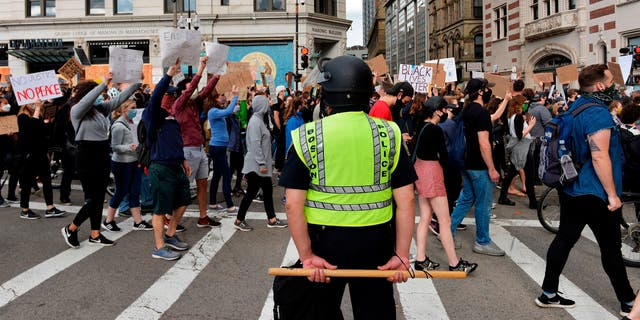 "A police officer holding a baton stands by as people march to call for Police Department reform as part of the ""Unite Against Racist Police Terror! Boston Speakout and March"" in Boston, Massachusetts on June 7, 2020. - Protesters have rallied for racial justice in cities across the United States following the death of George Floyd at the hands of police on May 25. (Photo by Joseph Prezioso / AFP) (Photo by JOSEPH PREZIOSO/AFP via Getty Images)"